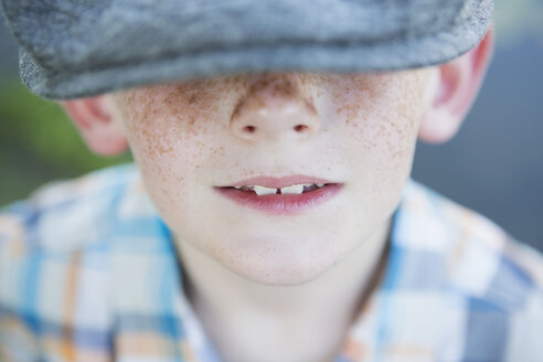 A young boy with a freckled nose, wearing a cap with a large brim. - MINF01529