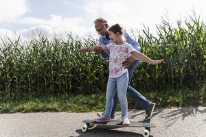 Mature man helping little girl to learn skateboarding - UUF14559