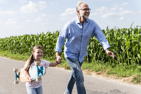 Mature man and little girl running on street, laughing - UUF14562