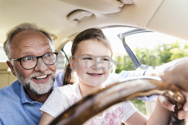 Little girl sitting on lap of grandfather, pretending to steer the car - UUF14565