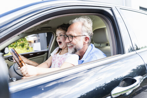 Little girl sitting on lap of grandfather, pretending to steer the car - UUF14571