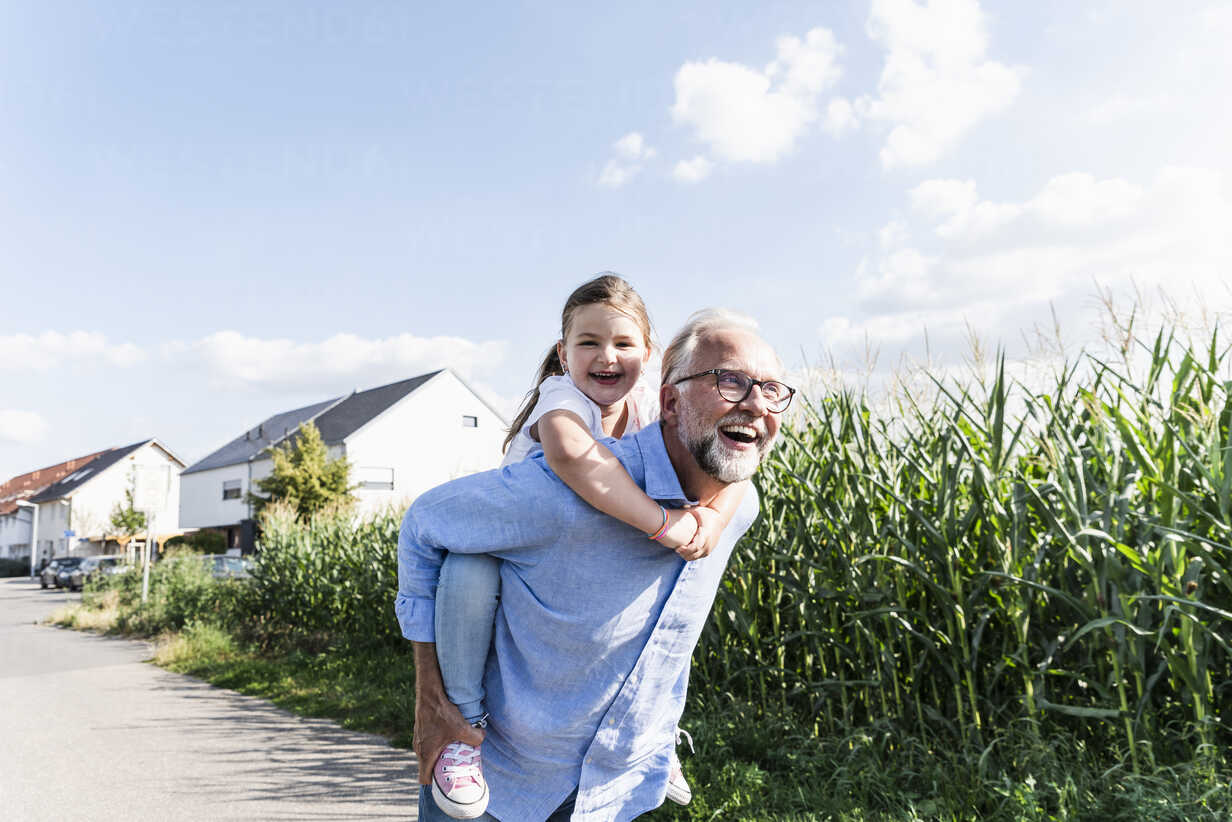 Grandfather carrying granddaughter piggyback - UUF14580 - Uwe Umstätter/Westend61