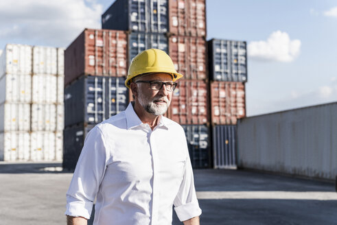 Businessman at cargo harbour, wearing safety helmet, portrait - UUF14583