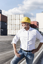 Businessman at cargo harbour, wearing safety helmet, portrait - UUF14586