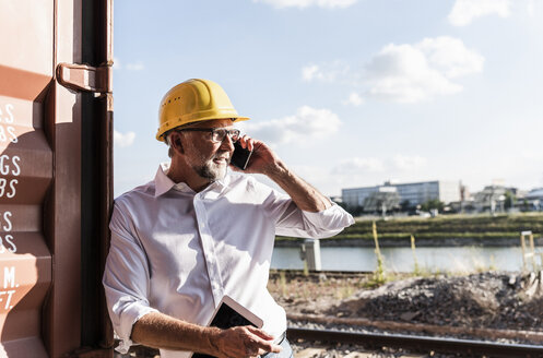 Businessman at cargo harbour, wearing safety helmet, using smartphone and digital tablet - UUF14598