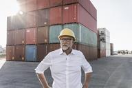 Businessman at cargo harbour, wearing safety helmet - UUF14604