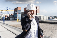 Businessman at cargo harbour, wearing safety helmet, using smartphone - UUF14613