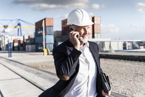 Businessman at cargo harbour, wearing safety helmet, using smartphone - UUF14613