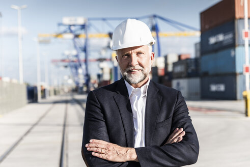 Businessman at cargo harbour, wearing safety helmet, arms crossed - UUF14616