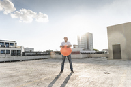 Mature man playing with orange fitness ball on rooftop of a high-rise building - UUF14631