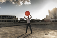 Mature man playing with orange fitness ball on rooftop of a high-rise building - UUF14634