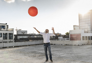 Mature man playing with orange fitness ball on rooftop of a high-rise building - UUF14637