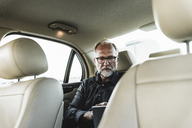 Mature businessman sitting on backseat in car, using digital tablet - UUF14640