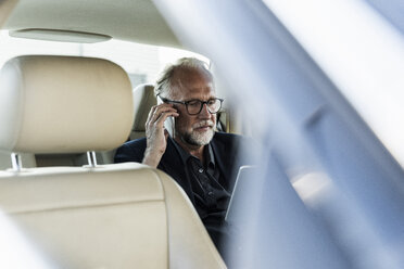 Mature businessman sitting on backseat in car, talking on the phone - UUF14643