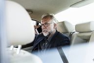 Mature businessman sitting on backseat in car, talking on the phone - UUF14649