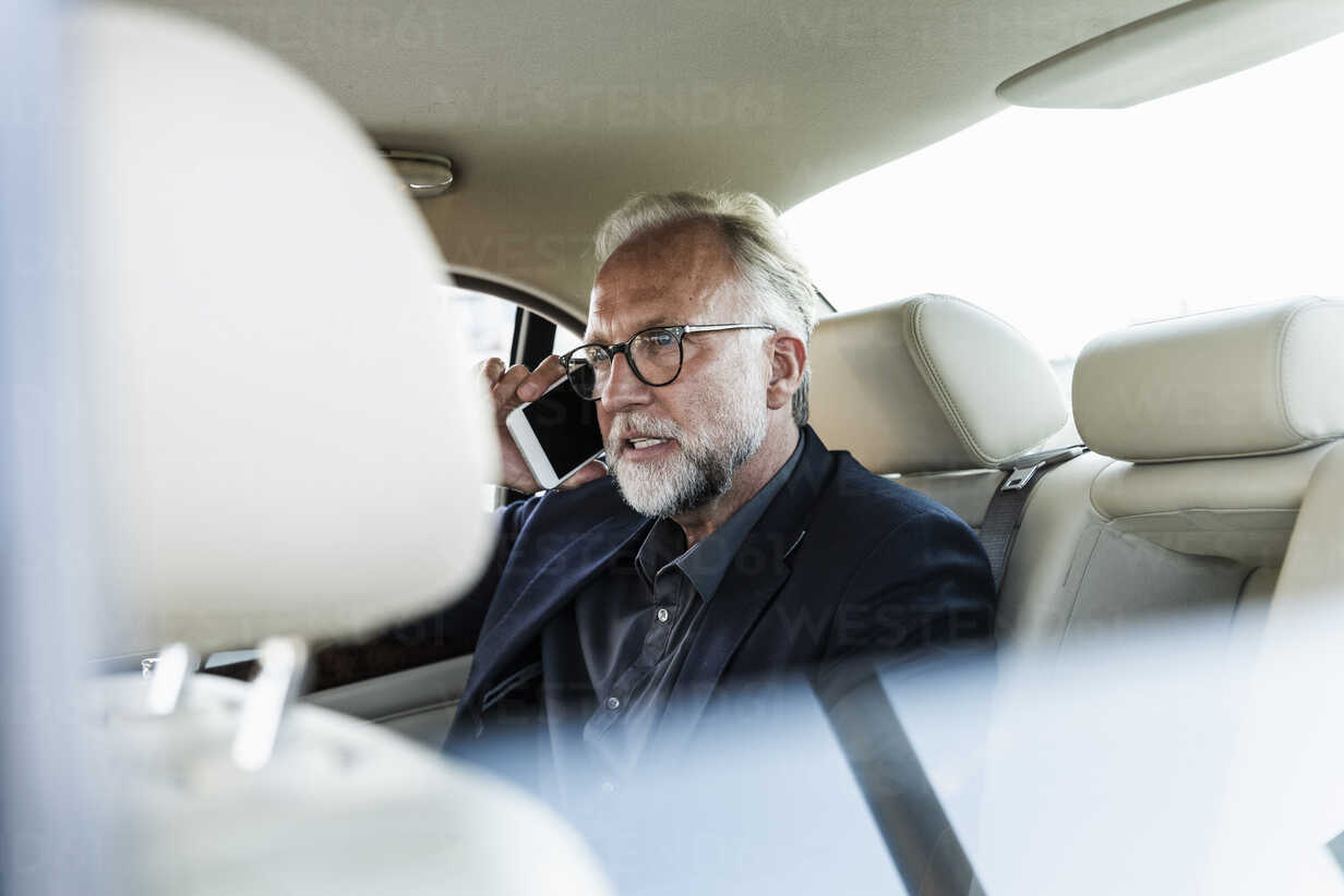 Mature businessman sitting on backseat in car, talking on the phone - UUF14649 - Uwe Umstätter/Westend61