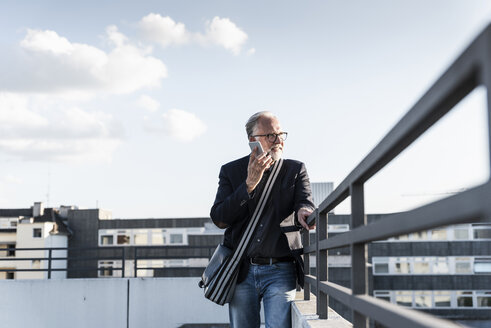 Mature man standing on rooftop, leaning on railing, using smartphone - UUF14652