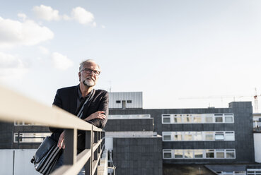 Mature man standing on rooftop, leaning on railing - UUF14655