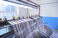 Multicoloured threads on industrial loom in textile mill - CUF43673