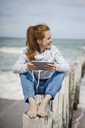 Woman sitting on fence at the beach,using digital tablet at the sea - KNSF04213