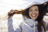 Woman having fun on a windy beach, wearing hood - KNSF04231