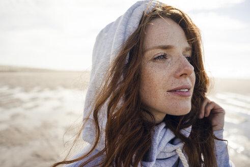 Woman wearing hood on a windy beach - KNSF04234