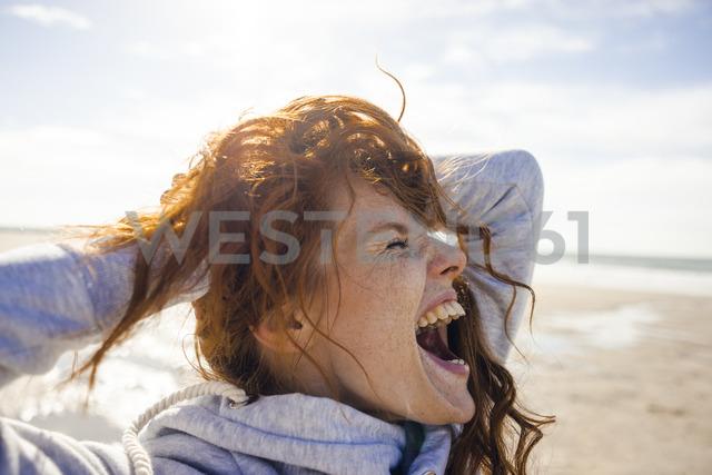 Redheaded woman enjoying fresh air at the beach - KNSF04243