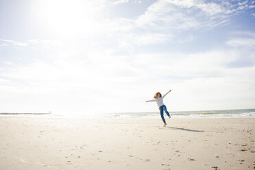 Happy woman having fun at the beach, dancing in the sand - KNSF04246