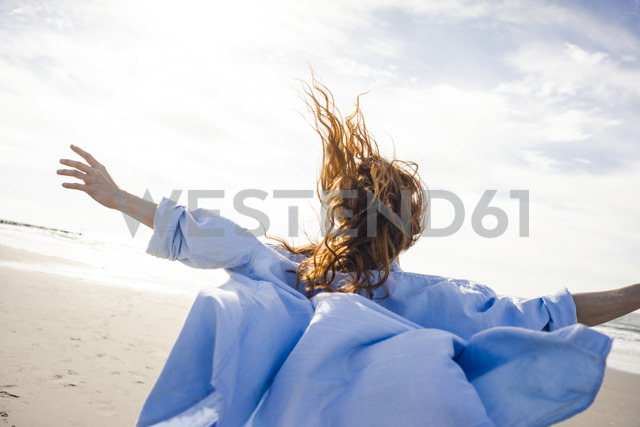 Woman running on the beach with arms out, rear view - KNSF04252