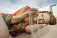 Redheaded woman lying on the beach, with sand trickling through her hand - KNSF04258