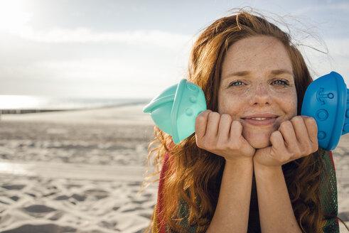 Redheaded woman lying on the beach with beach toys - KNSF04261