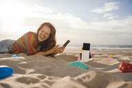 Redheaded woman lying on the beach with beach toys, using smartphone - KNSF04264