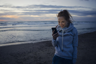 Woman using smartphone on the beach at sunset - KNSF04276