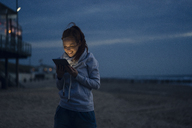 Woman using digital tablet on the beach at sunset - KNSF04279