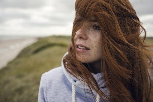 Redheaded woman enjoying fresh air at the beach - KNSF04282