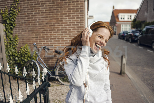 Redheaded woman using headphones in the city - KNSF04285