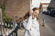 Redheaded woman using headphones in the city - KNSF04285
