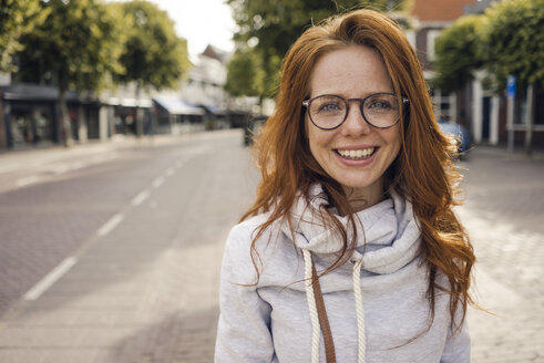 Redheaded woman with headphones in the city - KNSF04288