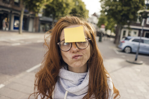 Redheaded woman with adhesive note sticking on her forehead - KNSF04291