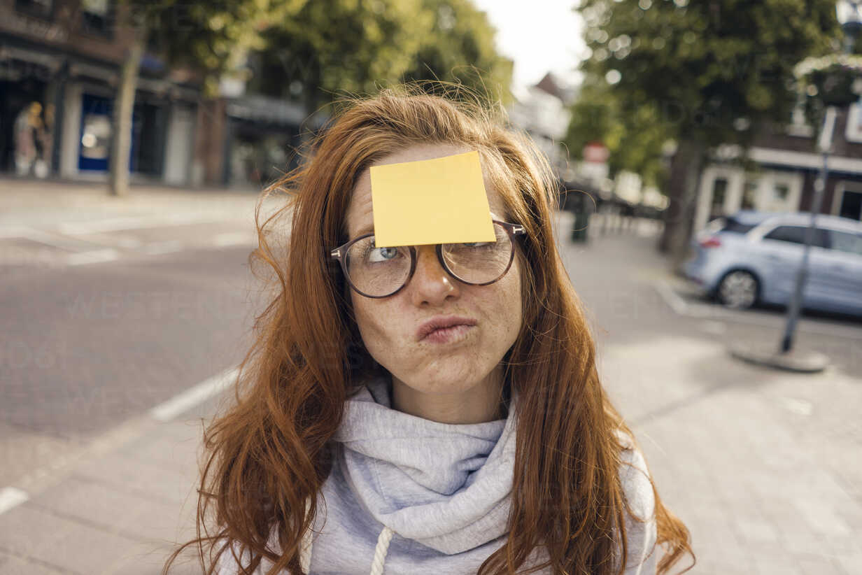 Redheaded woman with adhesive note sticking on her forehead - KNSF04291 - Kniel Synnatzschke/Westend61
