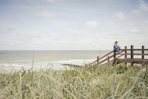 Woman sitting on fence at the beach, relaxing at the sea - KNSF04297