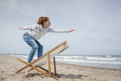 Woman standing on deck chair, pretending to surf - KNSF04303