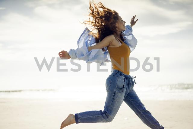 Happy woman having fun at the beach, jumping in the air - KNSF04327