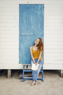 Redheaded woman sitting in front of beach cabin, reading a book - KNSF04330