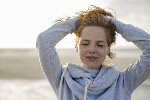 Redheaded woman enjoying fresh air at the beach - KNSF04336