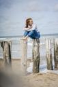 Woman sitting on fence at the sea, drinking tea - KNSF04339
