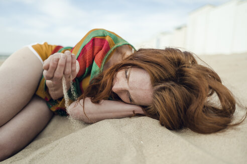 Redheaded woman lying on the beach, with sand trickling through her hand - KNSF04342