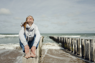 Woman sitting on fence at the beach, relaxing at the sea - KNSF04345