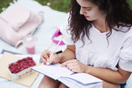 Young woman sitting on blanket on a meadow writing in notebook - ABIF00749