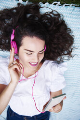 Smiling young woman lying on blanket listening music with smartphone and pink headphones - ABIF00752